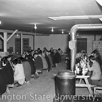 People seated in a mess hall at a farewell party for Julius Egashira