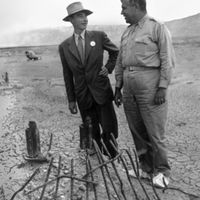 Oppenheimer and Groves examine the remains of one the bases of the steel test tower